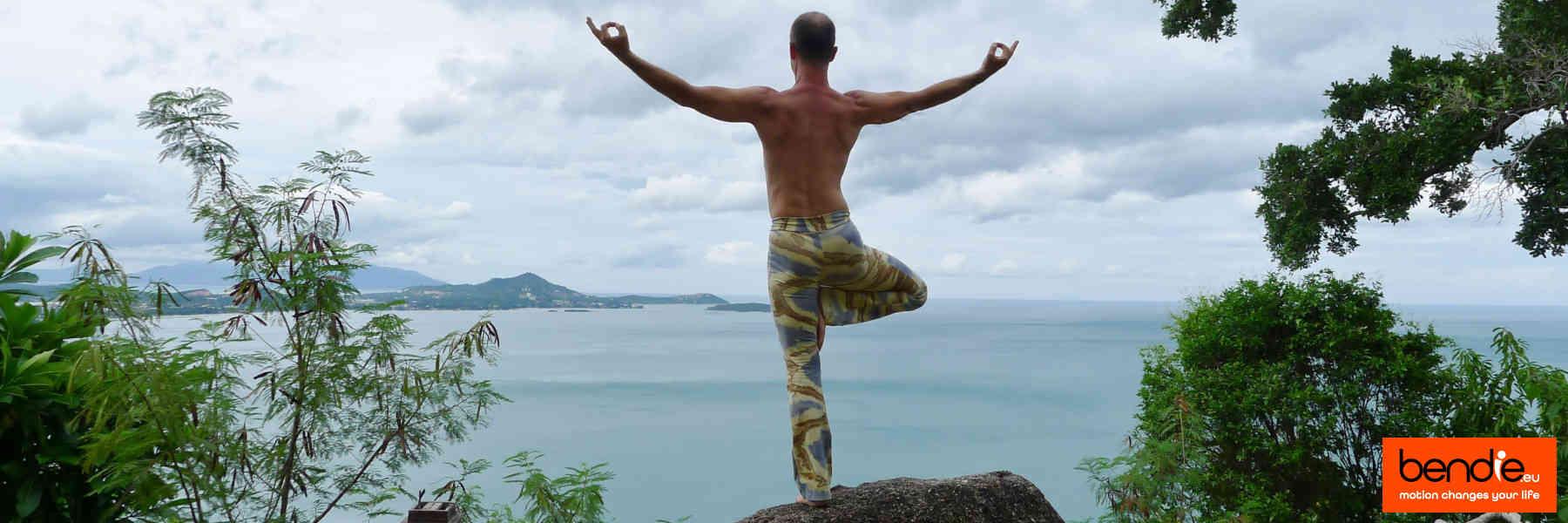 Informatie over Bendie. Staand op een rotsblok, de zee overkijkend in yoga houding.